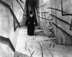 A frame from 'The Cabinet of Dr. Caligari' showing the style of German Expressionism, with a stark contrast and an erratic and angular mise-en-scene, Dr. Caligari walks through a long corridor, wearing a hat, suit and cane